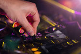 Fotografie DJ turntable console mixer controlling with two hands