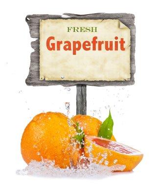 Fresh grapefruit in water splash on white