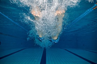 Legs of man jumping into pool