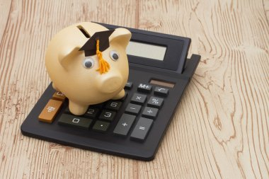A golden piggy bank with grad cap and calculator on wood backgro