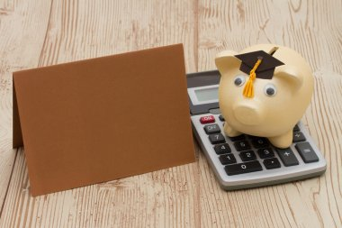 A golden piggy bank with grad cap, card and calculator on wood b