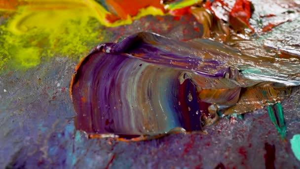 Mnohobarevné olejomalby na umělecké paletě.