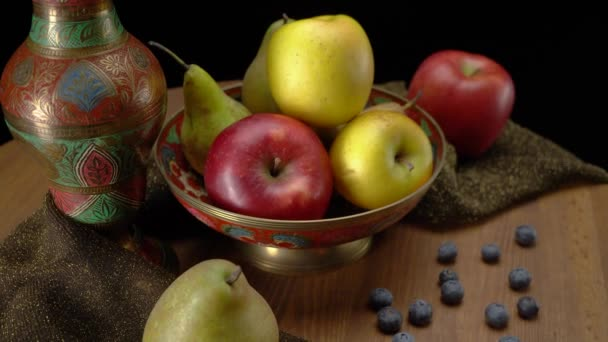 Still life with apples and pears on a black background.