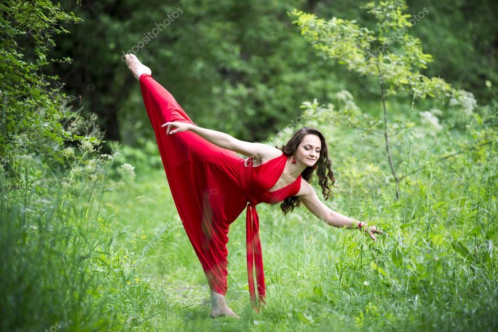 система девушка танцует в красном платье на природе пляже