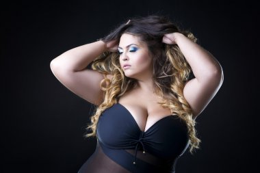 Young beautiful caucasian plus size model with big breast in black bra, xxl woman on dark background