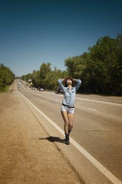 Young beautiful woman hitchhiking along a road