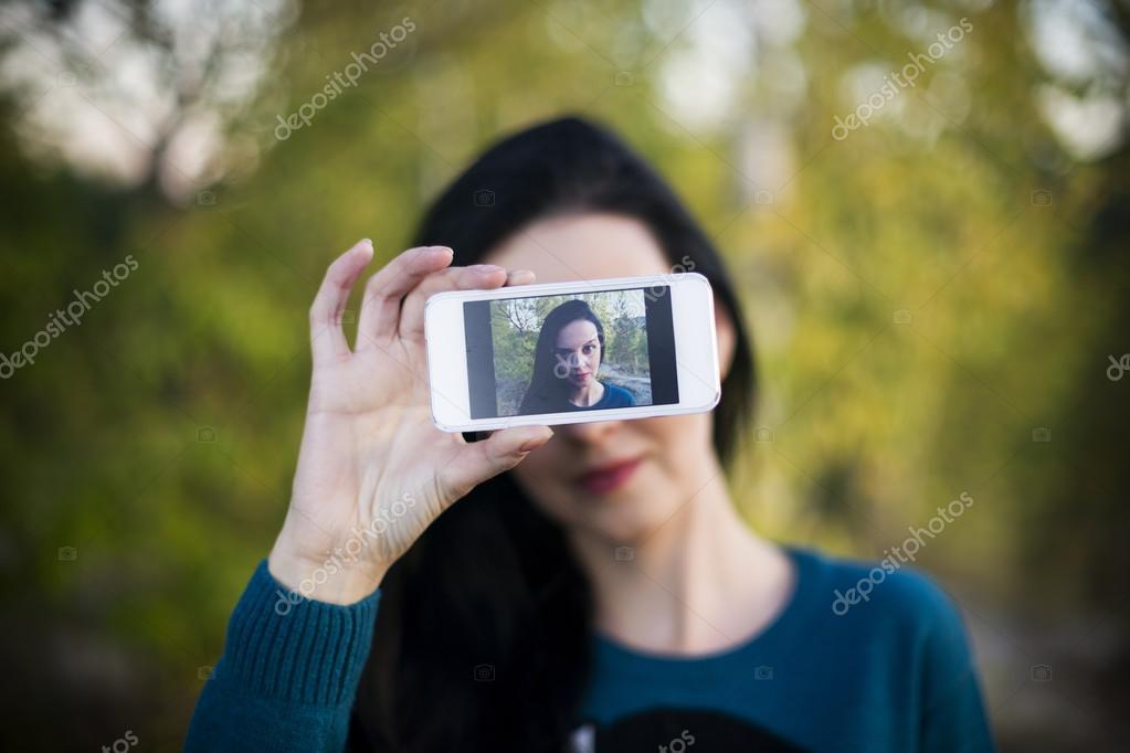 Beautiful young woman doing selfie outdoors
