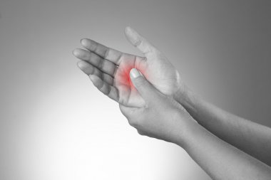 Pain in the joints of the hands. Carpal tunnel syndrome. Pain in the human body on a gray background