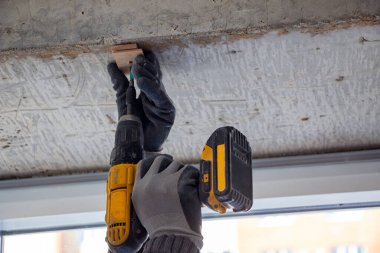 male hands of a construction worker tighten and fix  screws and self-tapping screw  with an electric cordless screwdriver for home improvement and building interior decoration.