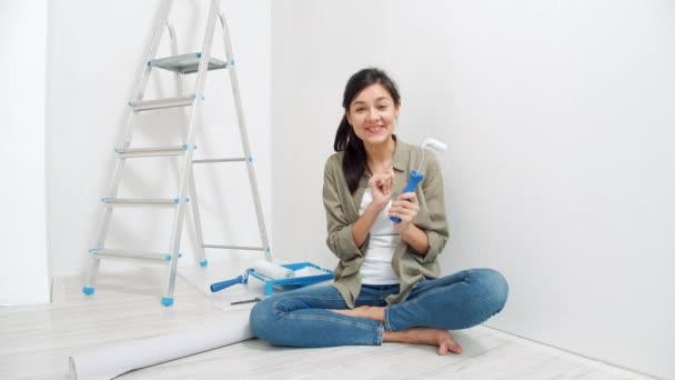 Portrét mladé usměvavé ženy, jak mluví o malířských rolích a nahrává video pro svůj vlog. Blogování, sociální média a koncepce renovace
