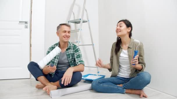 Mladý šťastný pár drží válečky s barvou a nahrává video pro jejich vlog. Koncept rekonstrukce, blogování a sociálních médií