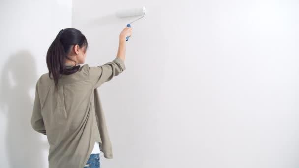 Junge Frau bemalt die Wand mit einer Walze. Blick von hinten. Do-it-yourself-Renovierung und neues Wohnkonzept. Kopierraum.