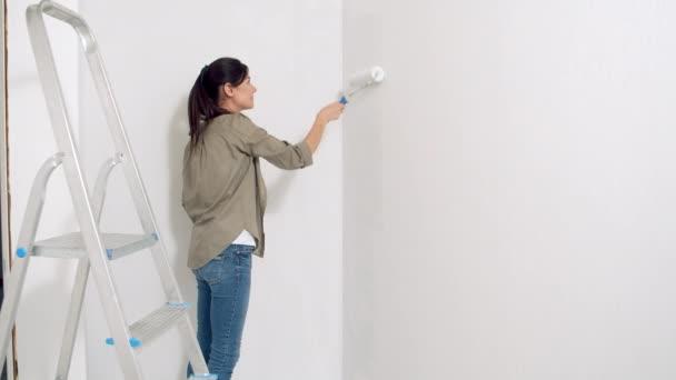 Junge Frau bemalt die Wand mit einer Walze. Neues Wohn- und Heimwerkerkonzept.