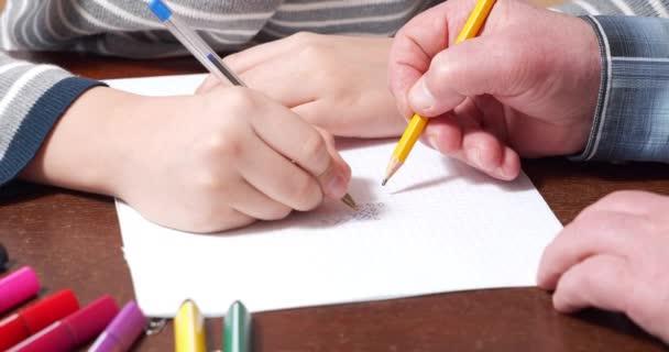 Közelkép gyerekekről és idős kezekről, amint tik-tac-tac-toe-t rajzolnak papírra. Szabadidő otthon.