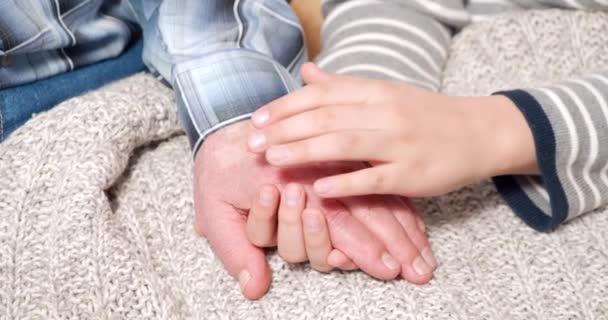 Nahaufnahme der Hände von Großeltern und Kind, die sich zärtlich halten. Kontinuität der Generationen