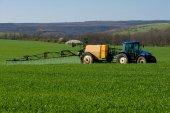 Traktor, rozprašování pesticidů v pšeničné pole