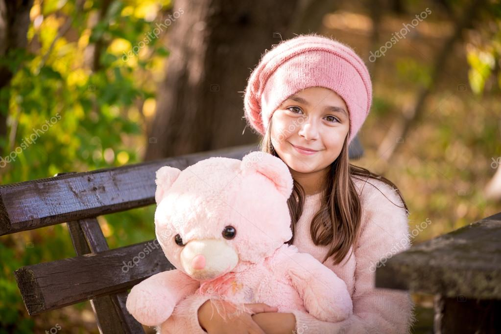 Adorable little girl outdoors at beautiful autumn day holding teddy bear