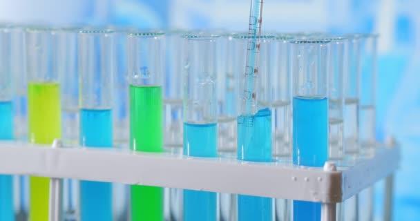 Laborasszisztens zöld folyadékot ad a kémcsőbe, figyelemmel kíséri a kémiai reakciót. A technikus óvatosan csepegteti az oldatot a pipettáról üvegcsövekbe DNS-elemzés céljából. Gyógyszerészeti Laboratórium