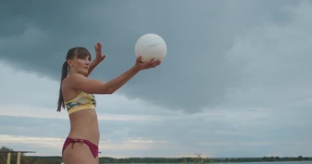 atletická žena oblečená sportovní bikiny hraje plážový volejbal, střední portrét v přírodě, útočící míč