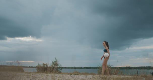 Beachvolleyball in der Natur, junge Frau serviert Ball auf Court gegen bewölkten Himmel, Athletin und Sportlerin