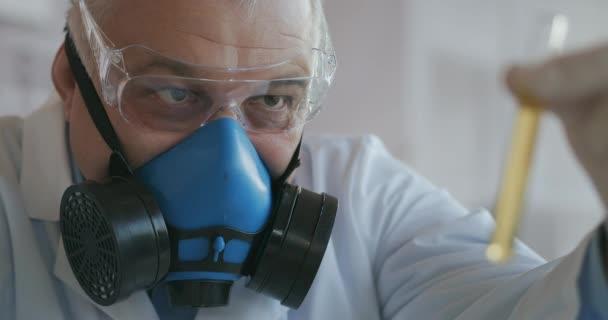 Ein Wissenschaftler eines Pharmaunternehmens, das Medikamente entwickelt, trägt eine blaue Atemschutzmaske und eine Schutzbrille, hält ein neues Medikament, ein Glasröhrchen mit einer gelben Flüssigkeit in den Händen und betrachtet es.