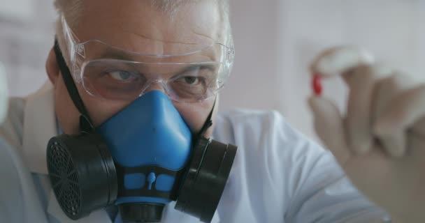 Ein Wissenschaftler eines Pharmaunternehmens, ein Medikamentenentwickler mit blauer Atemschutzmaske und Schutzbrille, hält ein neues Medikament in der Hand, eine rote Pille, und betrachtet es