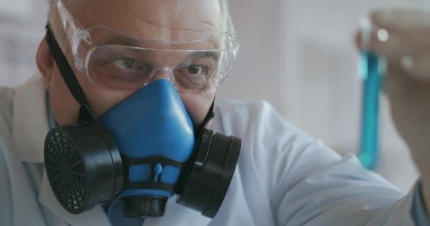Ein Wissenschaftler eines Pharmaunternehmens, das Medikamente entwickelt, trägt eine blaue Atemschutzmaske und Schutzbrille, hält ein neues Medikament in einer Glasröhre mit einer blauen Flüssigkeit in den Händen und betrachtet es.
