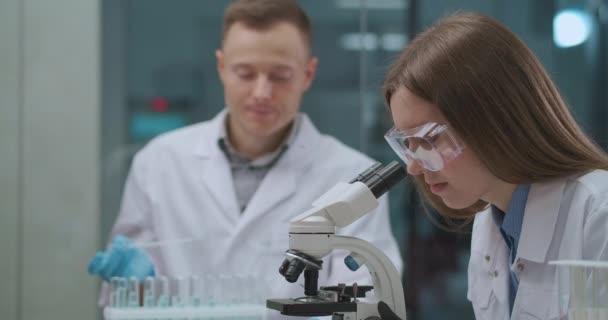 férfi és nő orvosi laboratóriumban dolgoznak, kémcsövekben vizsgálják a vegyi anyagokat, és mikroszkóppal vizsgálják a mintákat
