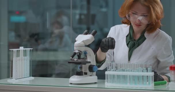 Labor für ökologische Expertise, Frau Spezialistin überprüft Wasserproben auf toxische und gefährliche, mit dem Mikroskop für die Forschung