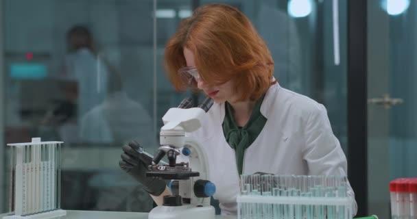 rothaarige Virologin erforscht Covid-19-Virus im medizinischen Labor und betrachtet es im Mikroskop