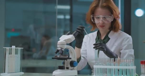 Frau arbeitet im chemischen Labor, testet Chemikalien unter dem Mikroskop, im wissenschaftlichen Labor für Experimente und Forschung