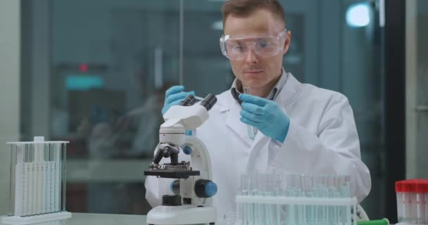COVID-19-Test im Labor, männlicher Techniker führt PCR und Serologie-Tests durch, mit Röhrchen mit Proben und Mikroskop