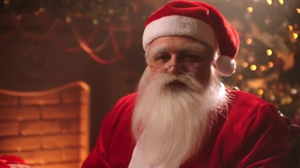 portrét roztomilého Santa Clause v rezidenci na severním pólu, stařec oblečený jako čaroděj se dívá kamerou laskavě