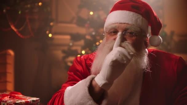 portré barátságos Mikulás díszített szobában karácsony este, öreg ember szürke szakáll tartja ujját a száj közelében tartani csendben