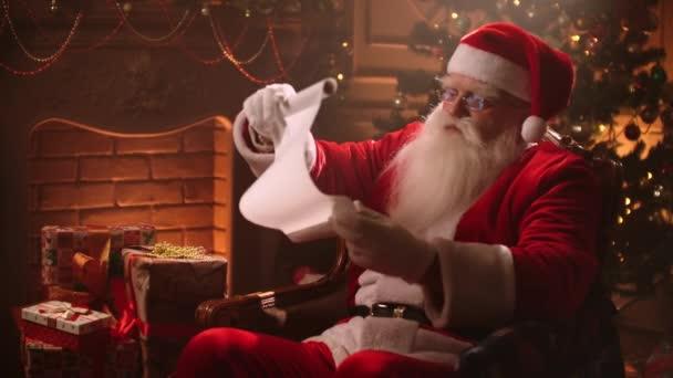 starší muž oblečený jako Santa Claus čte seznam přání v místnosti na Vánoce, drží dlouhý bílý list v ruce