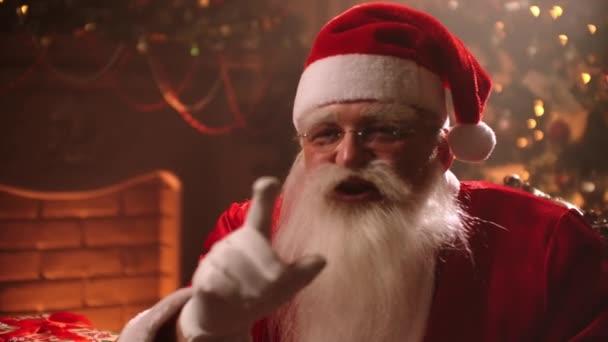 herec hraje roli Santa Clause, drží prst u rtů pro ticho na vánoční zdobené místnosti, ticho znamení na gestikulování