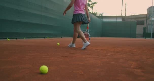 Detailní záběry ženských nohou ve sportovních teniskách a protézách na noze vyzvednutí tenisových míčků z hřiště