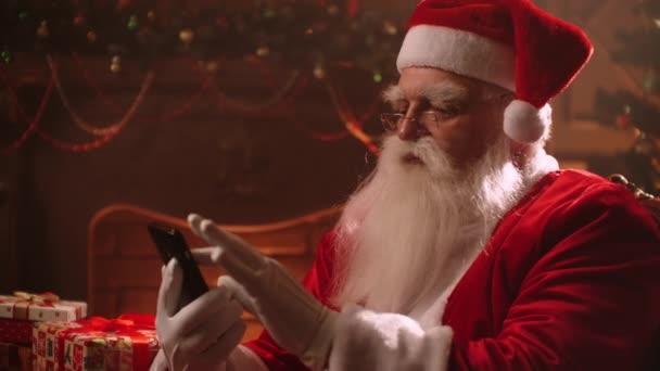 seriózní Santa Claus je swiping pomocí dotykové obrazovky smartphonu, pomocí moderní gadget pro komunikaci, portrét