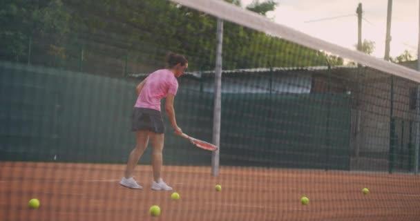 Ženský tenista sbírá míče na hřišti a prolamuje je sítí. Žena na hřišti a spousta roztroušených mečů
