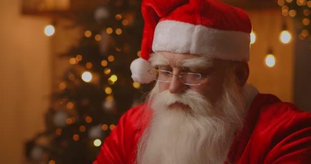 Jolly Santa arbeitet an einem Laptop-Computer. Weihnachtsmann mit Laptop, Nahaufnahme.