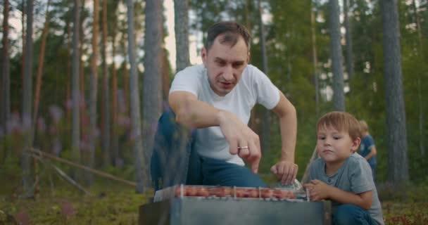 malý chlapec se dívá, jak jeho otec griluje klobásy, víkend v přírodě, muž a dítě odpočívají v lese