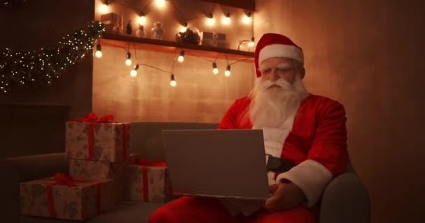 Der Weihnachtsmann arbeitet an einem Laptop und sitzt zu Hause auf dem Sofa im Hintergrund von Weihnachten. Weihnachtsmann reagiert auf Kinder-E-Mails