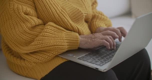 Ältere ältere Frau tippt eine Nachricht auf die Tastatur, Online-Webinar auf Laptop-Computer Fernarbeit oder soziales Fernlernen von zu Hause aus. Geschäftsfrau der 60er-80er-Jahre