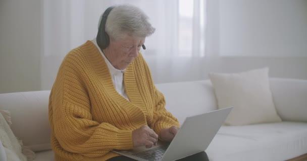 Idősebb nő ősz hajjal videóhívást kezdeményez laptoppal otthon. Idős nő, akinek videohívása van a családjával, mosolyog és integet. COVID 19 Maradj vonalban. Online csevegés barátokkal