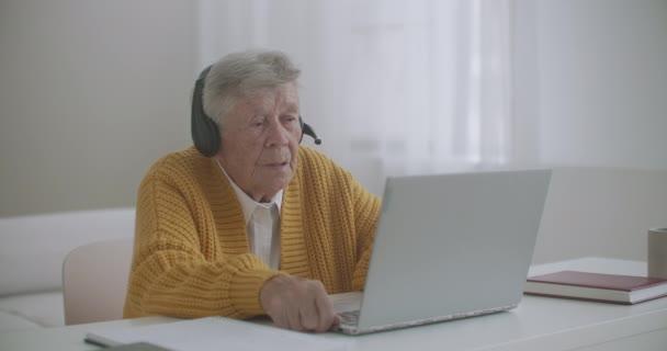 Eine ältere Frau benutzt einen Laptop, um Videoanrufe zu tätigen und gestikulierend Daumen-hoch-Handbewegungen im Haus zu zeigen. Alte Frau und modernes Gerätekonzept.