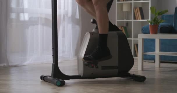 fitness doma muž je spinning pedály cvičení na kole v pokoji, detailní pohled na nohy, zdravý životní styl
