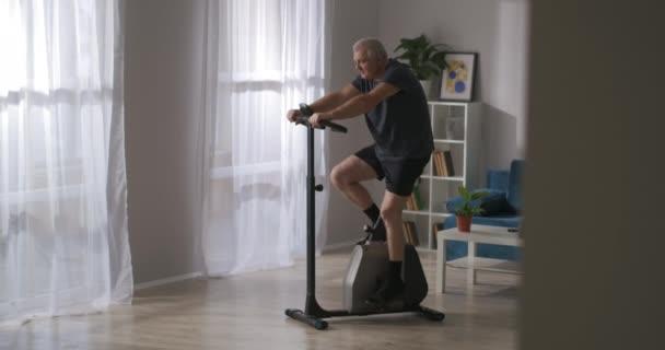 stationäres Fahrrad für zu Hause, Sportgeräte für die Gesundheit, erwachsener Mann trainiert allein im Wohnzimmer