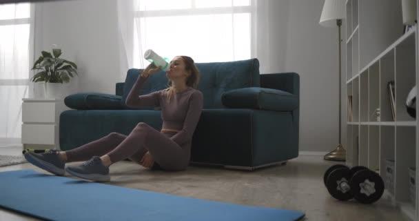 relax tělocvična králík sedí na podlaze po domácím tréninku o víkendech, pitné vody a odpočinku, sportovní žena v obývacím pokoji
