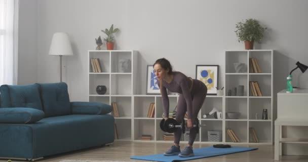 otthoni fitness edzés, felnőtt nő csinál billenő súlyzókkal a kezében, edzés a nappaliban, egészséges életmód