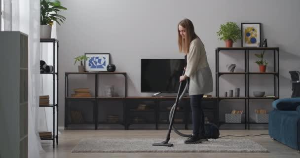 Hauswirtschaft in moderner Wohnung, Frau benutzt Staubsauger zum Reinigen des Teppichs im Wohnzimmer